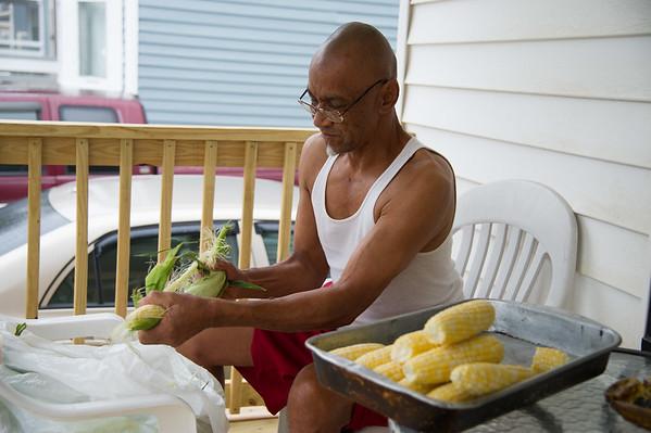 JOED VIERA/STAFF PHOTOGRAPHER-Lockport, NY-Roland Wiley shucks corn on his porch at Genesee Street.