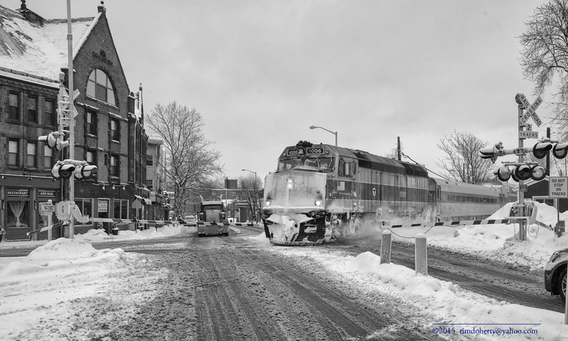 The first outbound Lowell Line train of Saturday heads across High Street in West Medford.