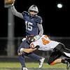 Oswego East quarterback Jaylon Banks (15) is sacked by Minooka linebacker Kenneth Kirkland (47) on Friday.