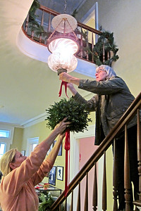 Donna Uher-Imperatore and Celia Radek hang a kissing ball at Israel Crane House & Historic YWCA