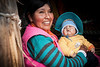 PERU - PUNO - 09/04/2015 - Mujer de la etnia UROS con vestimenta tradicional sostiene un bebe en su casa en isla flotante sobre el lago titicaca / Uros ´people woman holding a baby at her home on a floating island on titicaca lake / Peru : Frau der Ethnie der UROS in traditioneller Kleidung mit Baby in ihrem Haus auf einer der schwimmenden Insel auf dem Titicaca - See - Tititacasee © Bruno Bertagna/LATINPHOTO.org