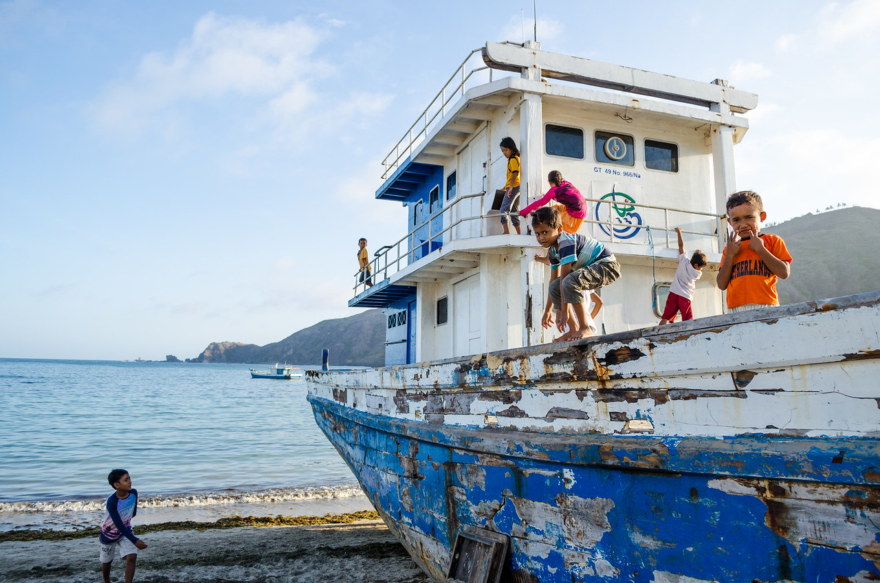 Kids playing on abandoned boat, Kuta, Lombok