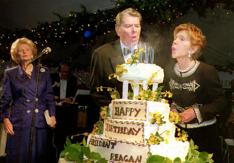 . With an assist from his wife Nancy, former U.S. President Ronald Reagan (C) blows out the candles on his cake February 6, 1993 as he celebrates his 82nd birthday. At left is former British Prime Minister Margaret Thatcher. The event took place at the Ronald Reagan Presidential Library and Center for Public Affairs.  (HAL GARB/AFP/Getty Images)