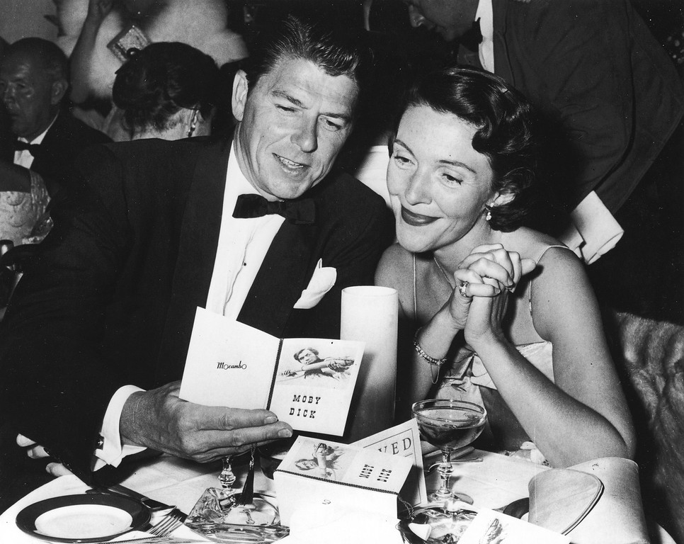 . American actor Ronald Reagan and his wife Nancy Reagan sit at a restaurant table, looking at a brochure at the premiere party for the film, \'Moby Dick,\' directed by John Huston, 1956. (Photo by Hulton Archive/Getty Images)