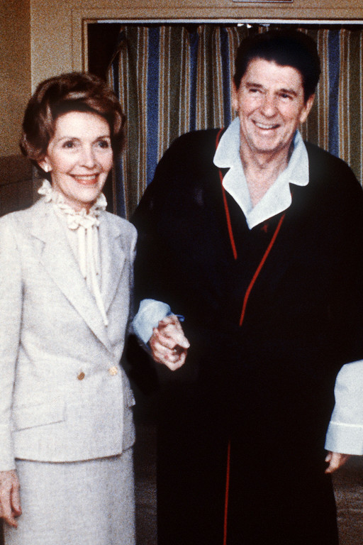 . This photo taken on April 3, 1981, shows President Reagan with Mrs Nancy Reagan inside George Washington University Hospital four days after the assassination attempt on him, in Washington, D.C.. Reagan was hit by one of six shots fired by John Hinckley, who also seriously injured press secretary James Brady (just behind the car).  Reagan was hit in the chest and was hospitalized for 12 days. Hinckley was acquitted 21 June 1982 after a jury found him mentally unstable. (MIKE EVENS/AFP/Getty Images)