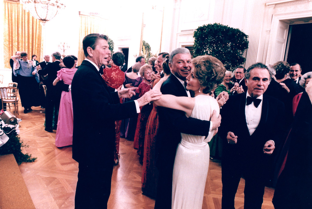 . President Ronald Reagan cuts in on singer Frank Sinatra, who dances with first lady Nancy Reagan during a party in the East Room of the White House on February 6, 1981.  Charles Wick, a friend of the Reagan\'s, walks by at right.  (AP Photo/White House photo, Mike Evans)