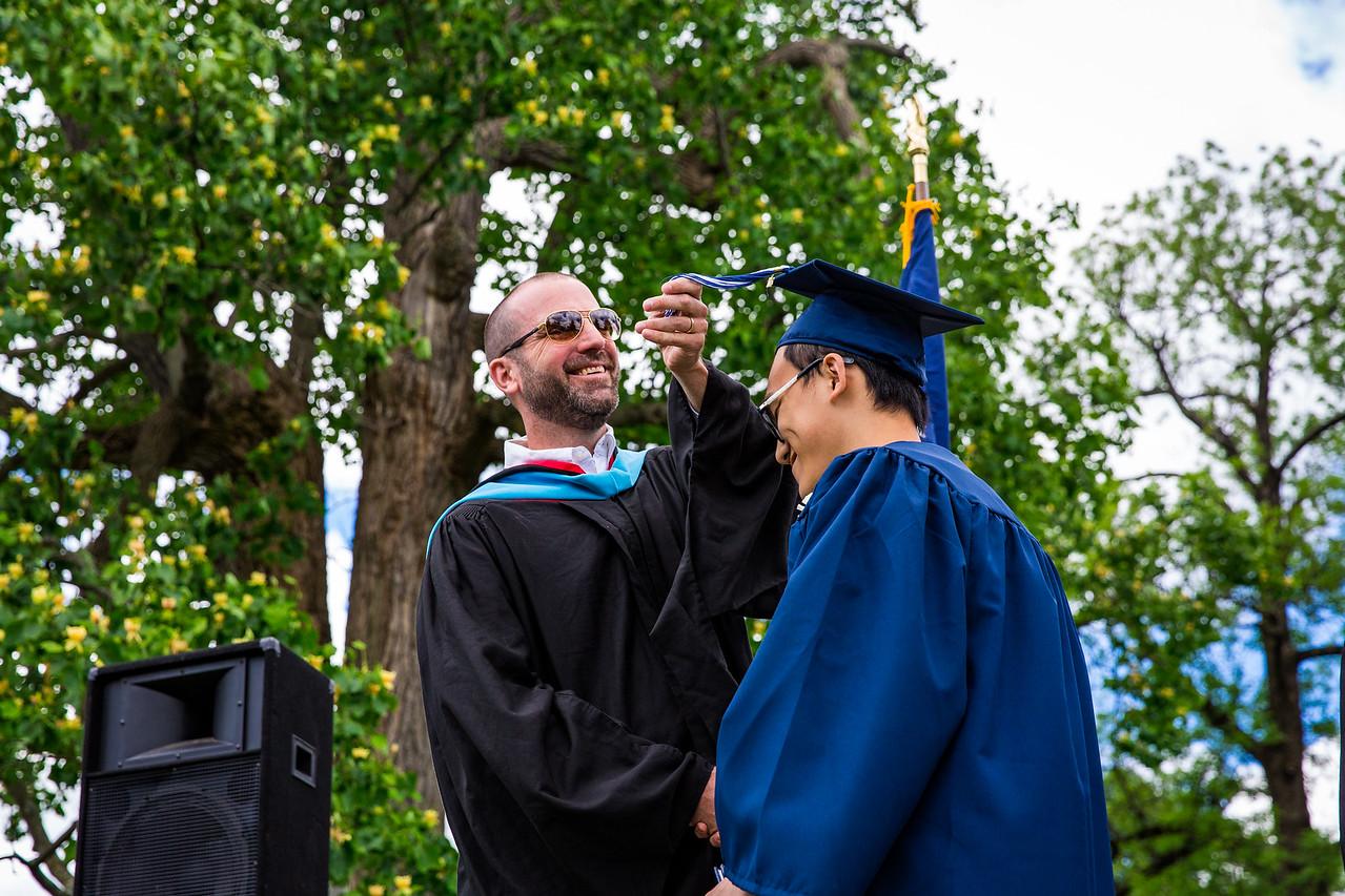 Mr. Lewis smiling as he flips the tassel of Peng Chen Lu