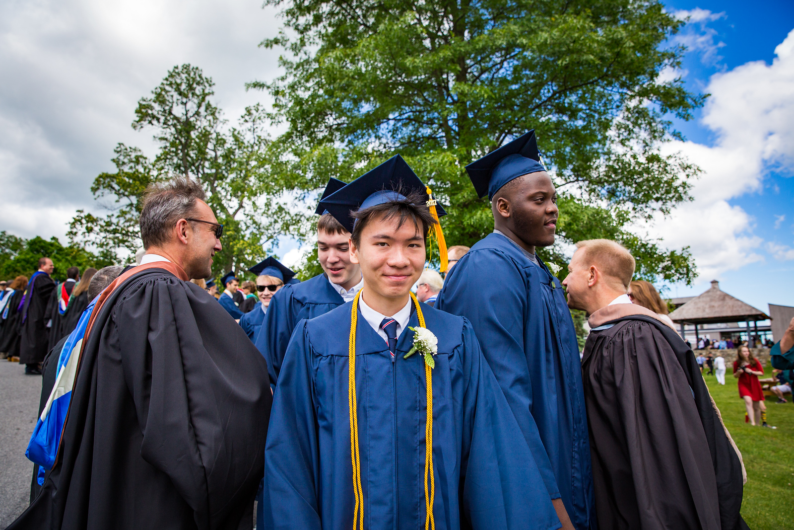 """Graduates Chuizheng """"Richard"""" Kong, Andrew Joseph Byrne and Christian Quartey are congratulated by faculty"""