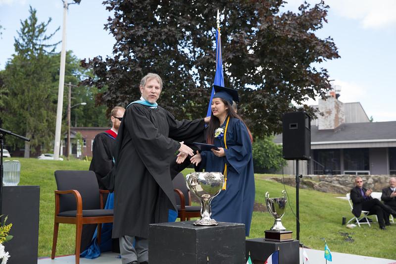 Headmaster Lamb congratulates Li Chen on receiving her diploma