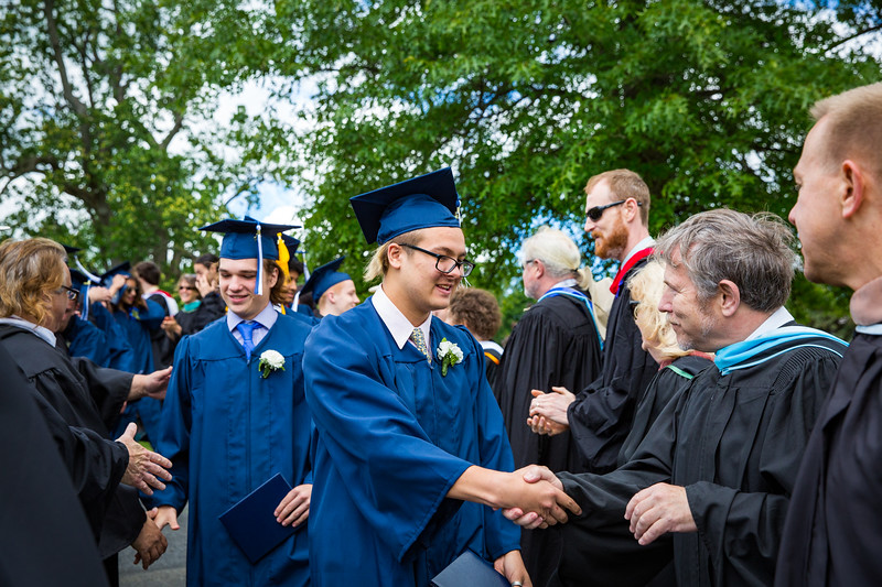 Graduates Garret Girardin and Dalibor Hanes are congratulated by faculty
