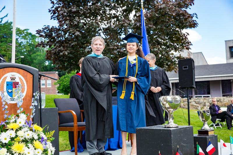 Headmaster Lamb congratulates Tsai-Hsin Chen on receiving her diploma