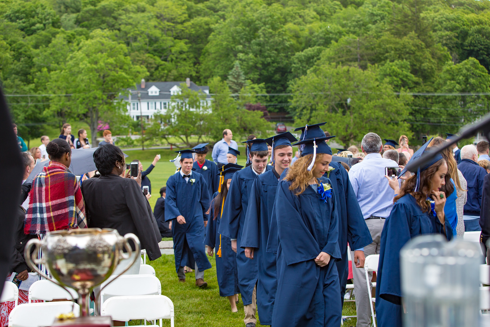 Seniors entering the graduation venue with Spy Rock House in the background