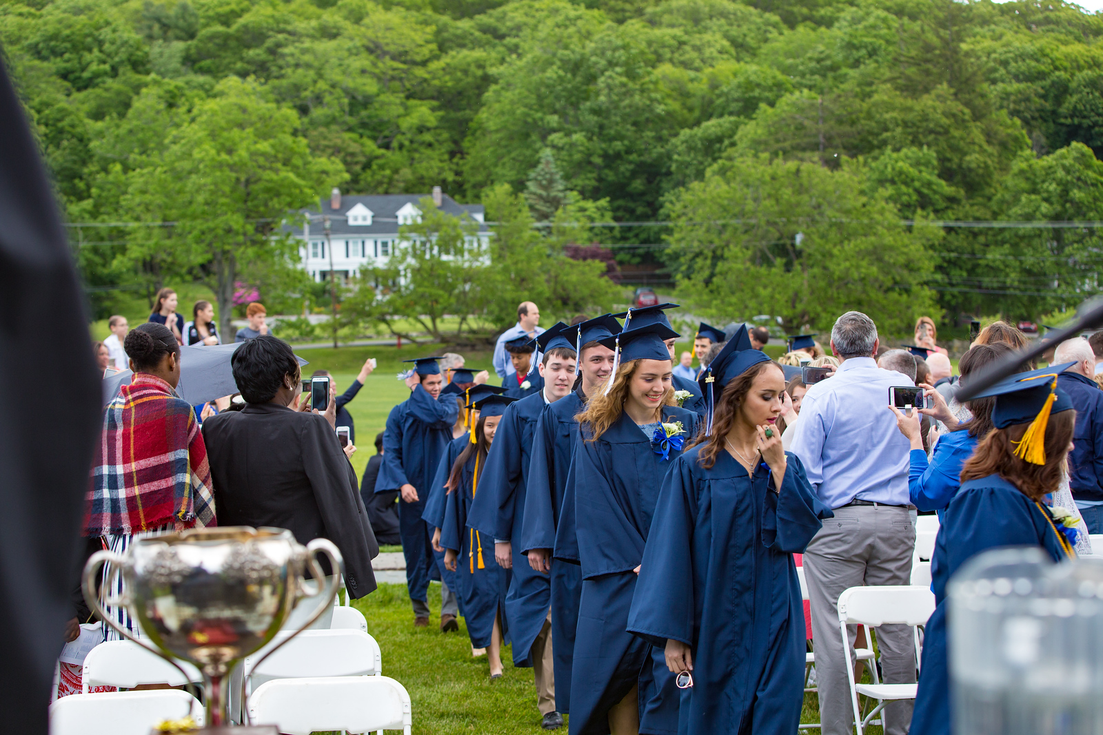 Seniors enter the graduation venue with Spy Rock House in the background