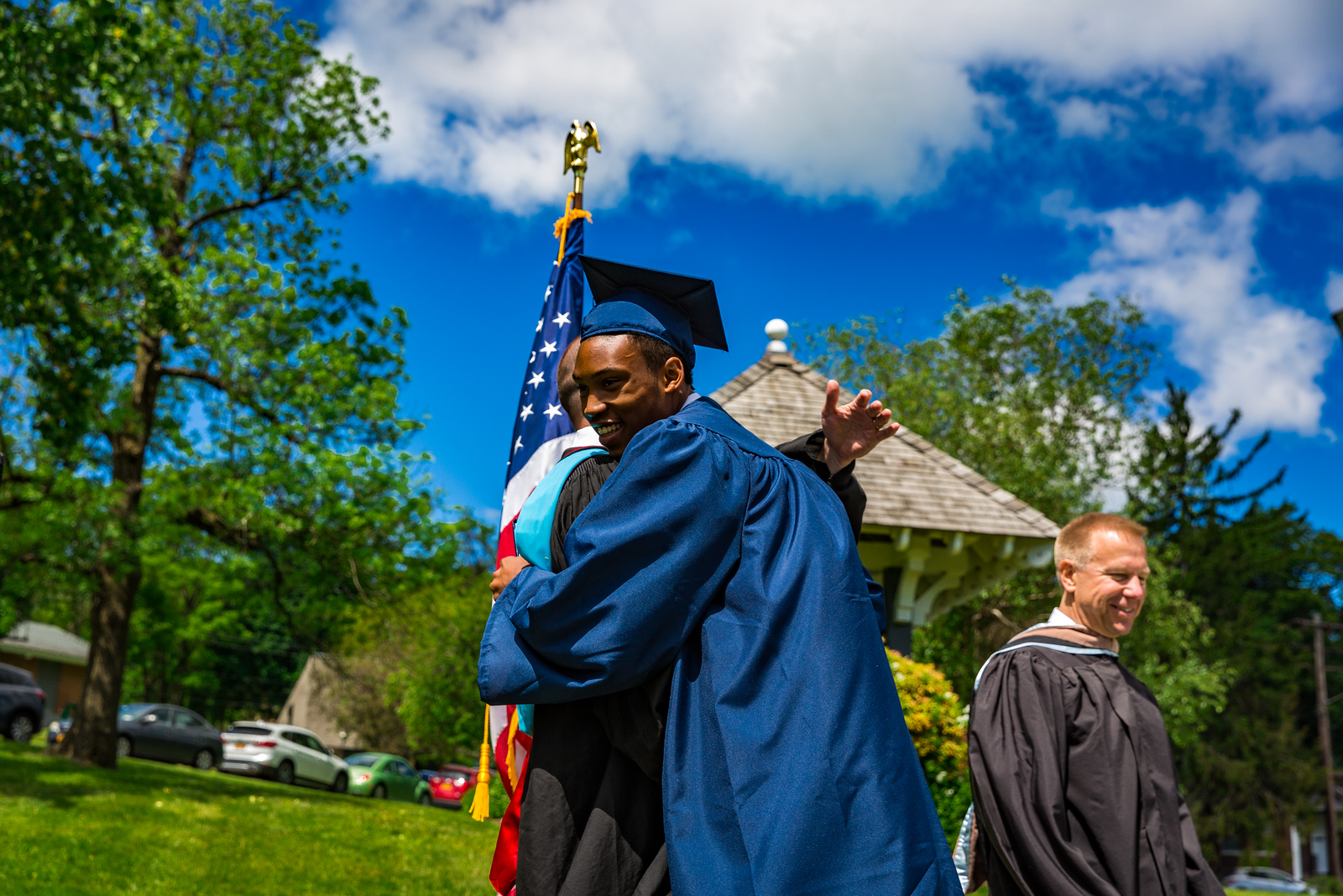 Mr. Lewis embraces Elijah Barnett on receiving his diploma