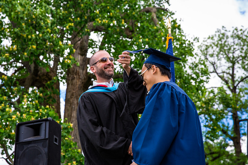 Mr. Lewis smiling as he flips the tassel of Peng Chen Lu