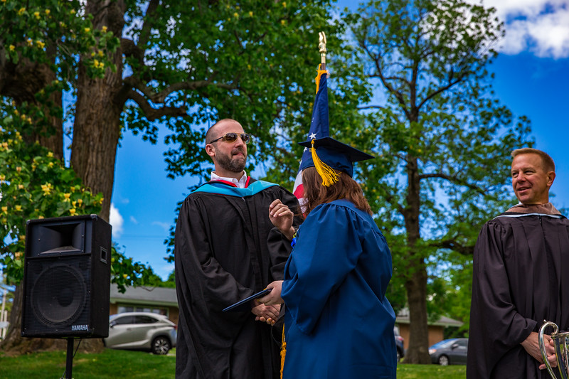 Mr. Lewis congratulates Victoria Bobrova on receiving her diploma as Col. Kopra looks on