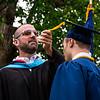 Mr. Lewis flipping the tassel of graduate Sebastian Zucker