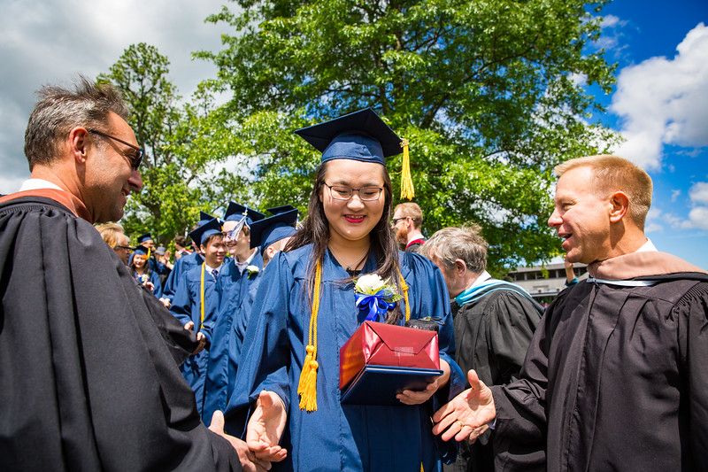 "Graduate Yunqui ""Vicky"" Liu is congratulated by Mr. Heno and Mr. Kopra"