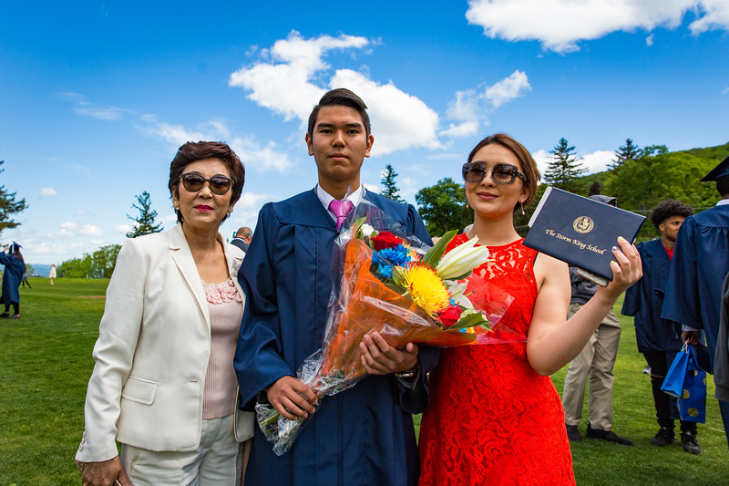 Graduate (center) Dimash Mukhamedi with his mother and sister.