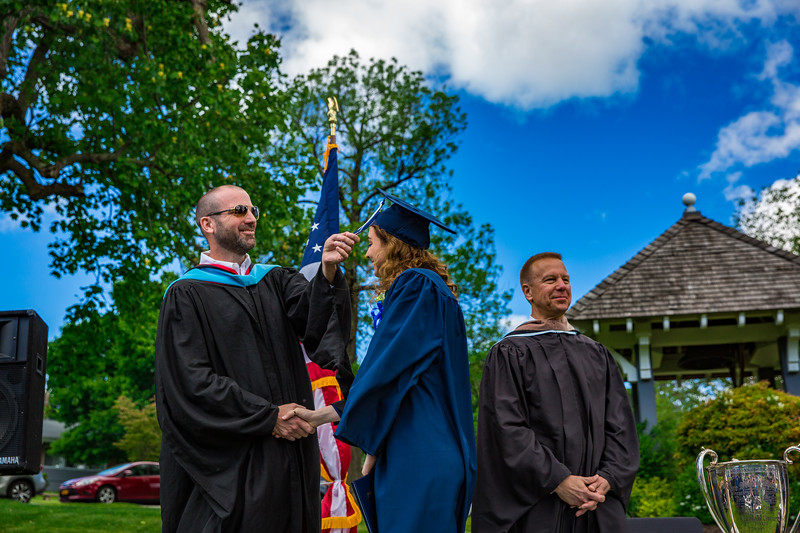 Mr. Lewis flipping Mariana Borbon-Bours' tassel from right to left as Col. Kopra looks on