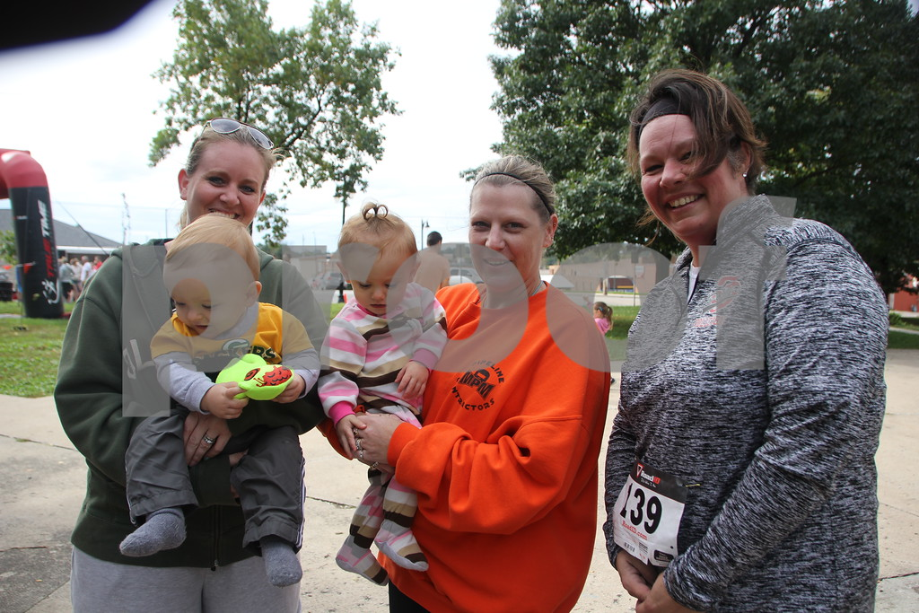 The 2016 Applefest Run took place at the city square by the Fort Dodge Library on Sunday, September 25, 2016. Along with participants that were running in the event there were refreshments available for runners after their run, and a few games for the kids complete with prizes. Seen here (left to right) is: Tania Elliott (in the green shirt) holding baby Easton Elliott (in yellow and gray shirt),  Marci Welter (in the orange shirt) holding baby Emerson Elliott ( in the striped outfit), and Kris Kirk.