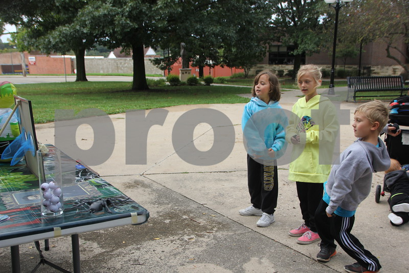 The 2016 Applefest Run took place at the city square by the Fort Dodge Library on Sunday, September 25, 2016. Along with participants that were running in the event there were refreshments available for runners after their run, and a few games for the kids complete with prizes. Pictured (in the gray jacket)  trying their hand at a game of bean bag toss is Piersun Black.