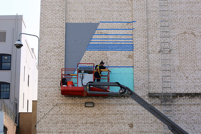 Jake Castro begins a mural on the back of the Crest Theatre