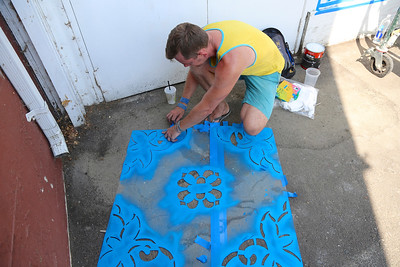 Muralist David Fiveash cleans a stencil on Day 1 of the Sacramento Mural Festival