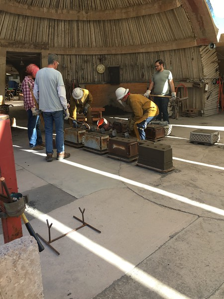 Pouring bronze into the sand molds for bells