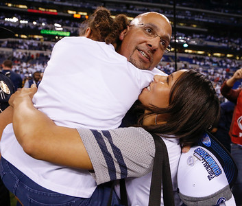 Penn State Nittany Lions head coach James Franklin gets a hug and kiss from his wife Fumi Franklin while hugging his daughter Shola Franklin during the second half of the Wisconsin Badgers against the Penn State Nittnay Lions for the Big Ten football championship at Lucas Oil Stadium in Indianapolis, Ind., Sunday, Dec. 4, 2016. Penn State won the game 38-31. (Photo by Sam Riche)