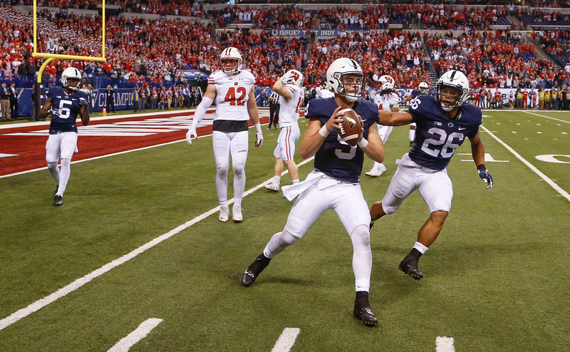 Penn State Nittany Lions quarterback Trace McSorley (9) runs out the clock to end the game with teammate Penn State Nittany Lions running back Saquon Barkley (26) during the second half of the Wisconsin Badgers against the Penn State Nittnay Lions for the Big Ten football championship at Lucas Oil Stadium in Indianapolis, Ind., Sunday, Dec. 4, 2016. Penn State won the game 38-31. (Photo by Sam Riche)