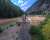 Drone shot of the Durango Silverton train tracks, coming out of the canyon and crossing over the Animas River.