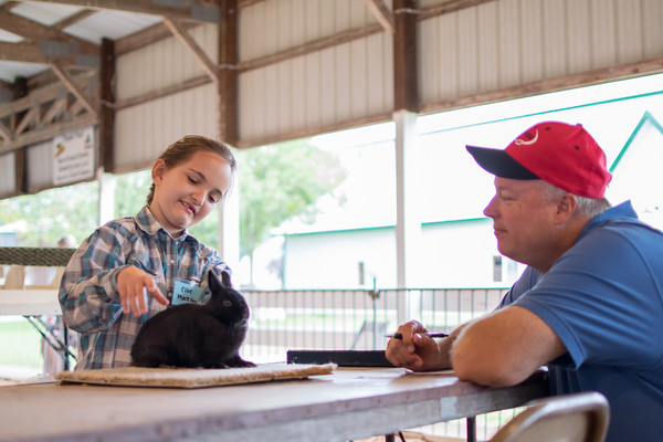 Ellie Macklin, left, talks to showmanship judge Dave<br /> Zimmerman about how she takes care of her rabbit.<br /> Trent Pearcy photo