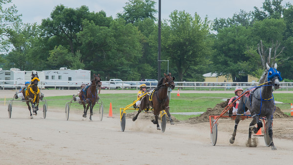 Four horses head down the final stretch of the race at the Effingam County Fair. Randal Fin and his horse Jaded Truth lead in first, followed by Darla Martin Lohman and her horse Queen Beatrice. In third and fourth are, respectively, Ray Gash and his horse Cruiser and Richard S. Finn and his horse Feel my Pain.<br /> Trent Pearcy photo