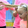 Korrie Hartke and her daughter Taylor measure the length of the pigtail of seven-year-old Myra Christie of Effingham during the Miss Pigtail competition Tuesday afternoon at the Effingham County Fair in Altamont. Christie won the with the longest pigtail at 29 inches.