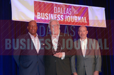 Kevin Rupp, CFO, Essilor of America, center, receives his award from Tony Banks and Larry king of ACG DFW.