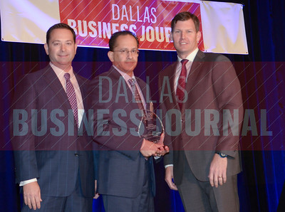 Mano Mahadeva, CFO, Solis Mammography, center, receives his award from Jason Downing and Dan Berner of Deloitte.