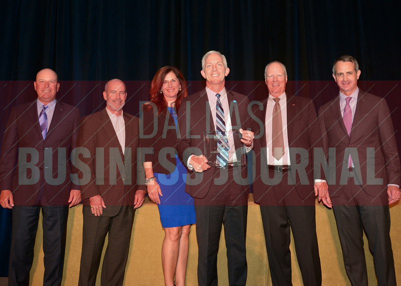 Lee Bird, CEO of At Home, center, picks up the housewares company's 9th place  Middle Market 50 award from Dickie Heathcott, partner Crowe Horwath, Larry King, president of the board of directors at ACG DFW, Kathy Schrock, managing partner of The CFO Suite, David Moore, president UMB Bank, Jon Henderson, Dallas managing partner Polsinelli, from the left.