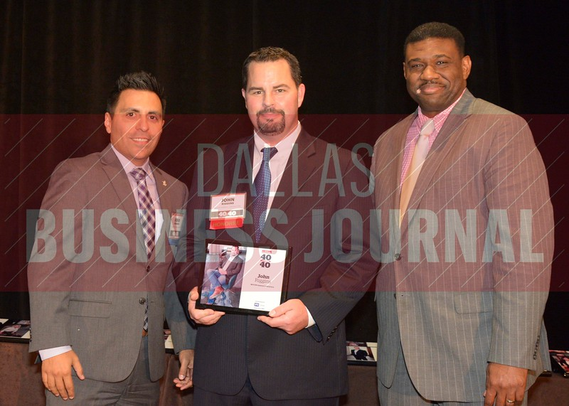 John Riggins receives his award from Jesus Miranda, Campus President universal Technical Institute, left and Kevin Davis, Director of EMBA Recruiting and External Relations at TCU.