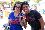 Two Florida Gators fans pose for the camera eating some waermelon given away at the Fan Zone propr to the University of Florida's annual spring gme, the Orange and Blue debut called Swamp Night this year.  April 8th, 2016.  Gator Country Photo by David Bowie.
