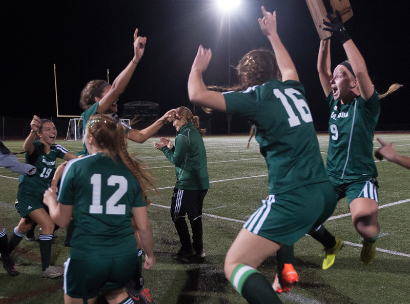 Nashoba Captain Caity Curtis (9) jumps for joy as she brings back the Div I Soccer Championship trophy to her teammates after defeating Wachusett in PKs. SENTINEL & ENTERPRISE / Jim Marabello