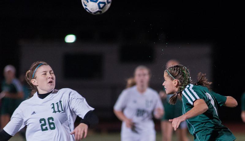 The glitter flies as Nashoba's Sarah Gilooly heads a ball away from Wachusett's Carolyn Heighton during the Div I Soccer Championship Game. Nashoba won on PKs. SENTINEL & ENTERPRISE / Jim Marabello