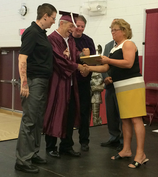 MARK ROBARGE - mrobarge@troyrecord.com Robert Fredette, second from left, is presented with his Lansingburgh High School diploma by school district Superintendent Cynthia DeDominick during the school's 114th commencement Friday night.