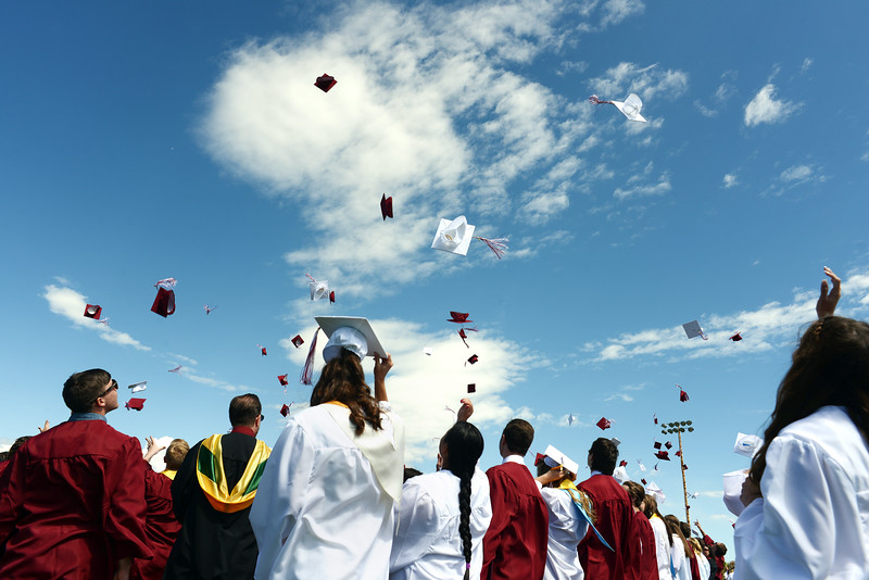 Graduates throw their hats in celebration following the Berthoud High School graduation Saturday at at Max Marr Stadium in Berthoud.