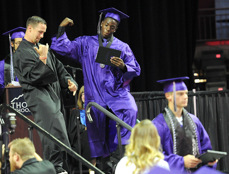 Mountain View High School graduate Logan Stewart and teacher Mike McMahon, left, do a quick dance on stage during the graduation ceremony Saturday, May 28, 2016, at The Ranch in Loveland. (Photo by Jenny Sparks/Loveland Reporter-Herald)