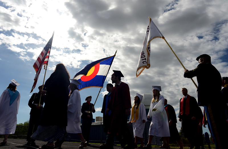 Teachers and graduates walk past the Berthoud High School Army JROTC Color Guard during the Berthoud High School graduation Saturday at at Max Marr Stadium in Berthoud.