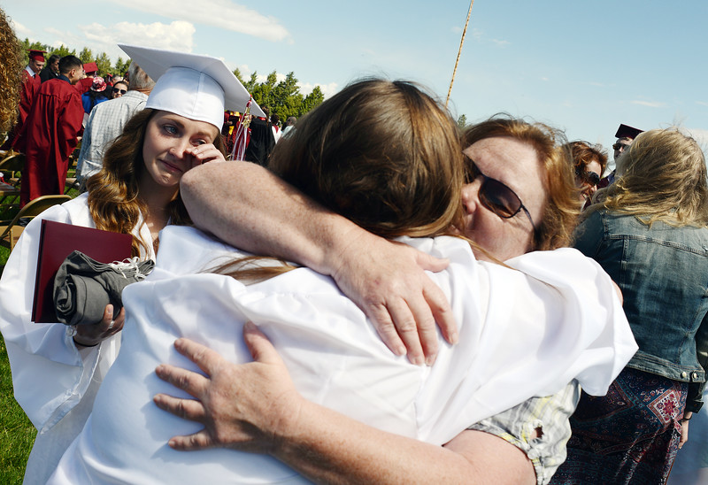 Alissa Krause, 18, left, wipes away a tear as fellow graduate Kali Scherer, 17, foreground, hugs her mother, Monika Scherer during the Berthoud High School graduation Saturday at at Max Marr Stadium in Berthoud.