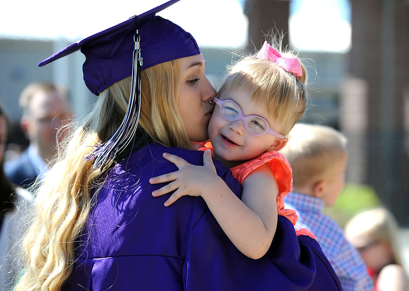 Mountain View High School graduate Emma Wilson, left, gives her cousin, Karlynn Dees, 3, a smooch after her graduation ceremony Saturday, May 28, 2016, at The Ranch in Loveland. (Photo by Jenny Sparks/Loveland Reporter-Herald)