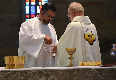 Frater Juancho assists in preparing the altar