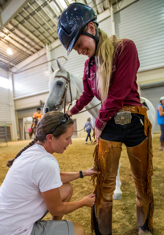 . Alyssa Jones, right, from Wellington, gets assistance with her chaps from Christy Nichols, left, Tuesday afternoon August 2, 2016 at the Ranch-Way Feeds Indoor Arena & Pavilions during 4H activities for the Larimer County Fair and Rodeo in Loveland. (Photo by Michael Brian/Loveland Reporter-Herald)